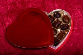 pic of valentine candy  - A heart shaped box of chocolates over a red background.