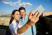 Young affectionate couple looking at camera in smartphone while making selfie on roof poster