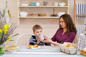 Mother Feeds Her Son. Mother And Son Having Breakfast. Happy Mother And Son In The Kitchen. Concept  poster