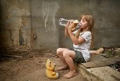 Poor Thirsty Homeless Girl Drinking Water From Plastic Bottle In The Dirty Alley, Selective Focus. P poster