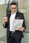 Confident Businessman Looking Through News During Coffee Break. Young Caucasian Man In Formal Suit W poster