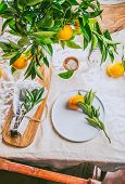 Table Setting With White Plate, Cutlery, Linen Napkin And Orange Tree Branch Decoration On White Lin poster