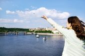 Prague. The sight from the Karlov bridge. The girl throws a coin to return to this place again.