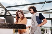 Joining Wife. Curly Dark-haired Man Wearing Sunglasses Joining Her Wife At Work While Sitting In The poster