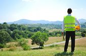 Construction worker on hill with country road