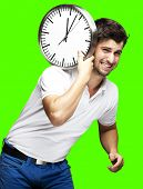 portrait of a handsome young man carrying a clock against a removable green chroma background