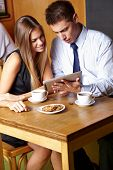 Two business people working with tablet computer in a caf�?�©