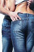 Vertical shot of a seductive couple wearing jeans which accentuate beautiful form