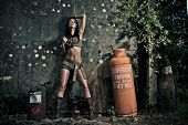 Gritty dramatic portrait of a sexy woman in skimpy shorts and boots posing against a grungy wall wit