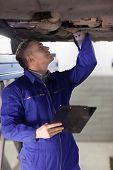 Mechanic looking at the below of a car while holding a clipboard in a garage