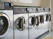 stock photo of oversize load  - row of steel front loading washers in a laundromat