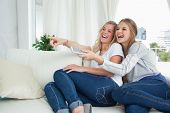 ein paar Mädchen auf der Couch lächelnd, wie sie Fernsehen