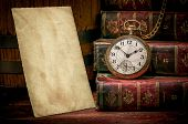 foto of low-light  - Vintage wood desk with old photo paper texture books and old pocket clock in low - JPG
