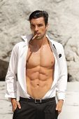 Sexy male model in open shirt exposing great toned muscular body and abs