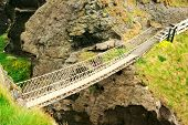 picture of old bridge  - A view of a primitive rope bridge spanning chasm - JPG