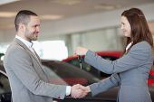 Man receiving car keys while shaking hand in a dealership