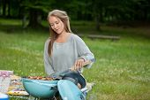 Cute young woman in casual wear cooking food on a portable barbecue in park at weekend outing