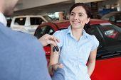 Frau lächelt, als sie jemand schüttelt übergeben in einem Autoshop
