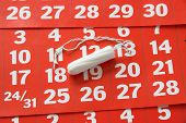 picture of tampon  - The sanitary tampon lying on a red calendar - JPG