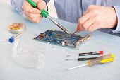 Man using soldering tool for the computer parts.