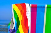 a swimsuit patterned with the rainbow flag on a deck chair of different colors on the beach