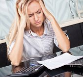 stock photo of frustrated  - Sad woman looks at the bill - JPG