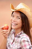 Peach eating cowgirl happy. Portrait of American cowgirl eating peach or nectarine fruit smiling and laughing wearing cowboy hat outside. Healthy eating concept with multiracial Caucasian Asian girl