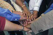 stock photo of huddle  - Hands of businesspeople in huddle - JPG