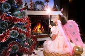 picture of cozy hearth  - little fairy girl with magic wand near a Christmas tree fireplace on background - JPG