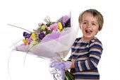 Smiling boy with a bouquet of flowers as a gift for birthday, mothers day or valentine's day