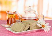 Tasty halva with tea on table in room