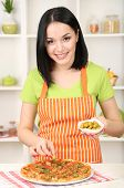 Girl housewife with delicious pizza on kitchen background