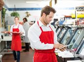 Male butcher using digital tablet at store with colleagues working in background