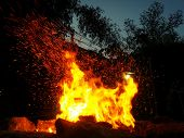 picture of torchlight  - Sparks bounce off from a bonfire at night after a log thrown into it - JPG