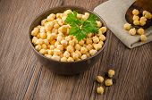 stock photo of chickpea  - Chickpeas on ceramic bowl on dark wooden background - JPG
