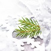 Christmas Tree Branch And White Christmas Ornaments On Soft Grey Background. Christmas Time Decorati
