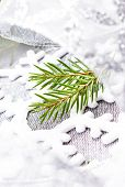 Christmas Tree Branch And Silver Ribbon Close Up. White Christmas Ornaments On Soft Grey Background.