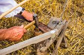 picture of scythe  - Man is sharpening a scythe which is used to mow grain - JPG