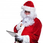 santa claus looking very thoughtful while reading wishes on his tablet pad computer