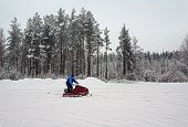 Man on a snowmobile on a skiing run.