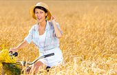 stock photo of riding-crop  - Girl rides bicycle with flowers in rye field - JPG