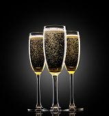 Glasses of champagne on black background