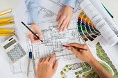 foto of blueprints  - Close Up Of Two Architects Discussing Plan Together At Desk With Blueprints - JPG