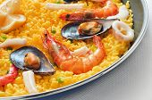 closeup of a typical spanish paella, with seafood and vegetables, in a paellera, the paella pan