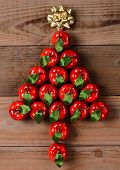 Overhead view of a group of red apple Christmas ornaments in a Christmas Tree shape. The ornaments are on a rustic wood floor with a gold bow at the top. Vertical format.