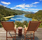 Charming rural idyll. Clouds reflected in the smooth water of the river. A comfortable place to enjoy the beauty of the landscape. Two wooden chairs - on a wooden platform