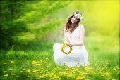 Image Of Pretty Woman In A White Dress Weaves Garland From Dandelions In The Field, Happy  Cheerful