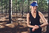 Woman runner checking pace on gps sports watch in forest