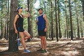 Couple take rest to drink water after running marathon on trail
