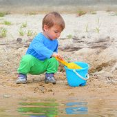 stock photo of spade  - Little boy playing with bucket and spade on the beach - JPG